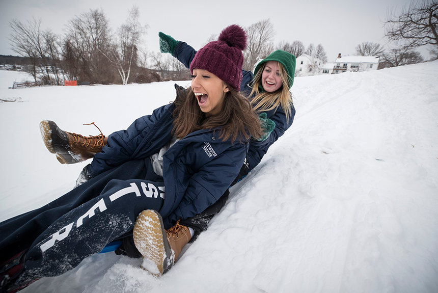 Students sledding down hill on Brewster campus