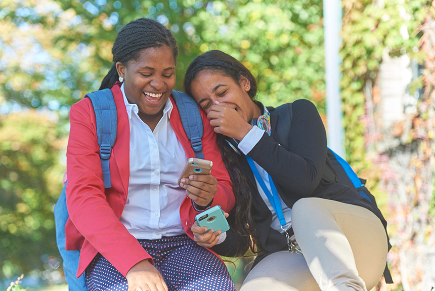 Two Brewster students laughing and looking on phones
