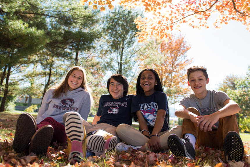 Brewster students sitting in fall leaves