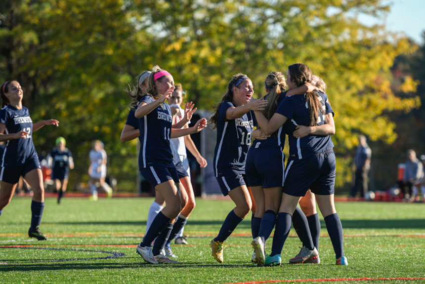 Brewster girls' soccer celebrating on turf field